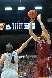 December 11, 2013: New Mexico State Aggies guard Kevin Aronis (5) takes a three point shot over Arizona Wildcats guard T.J. McConnell (4) in a game between No. 1 Arizona and New Mexico State at McKale Center in Tucson, Ariz. Arizona defeated New Mexico State 74-48.