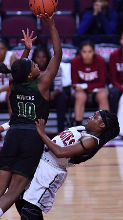 LAS VEGAS, NV - MARCH 07:  Tonishia Childress #3 of the New Mexico State Aggies tries to draw a charge against Tyeshia Bowers #10 of the Chicago State Cougars a quarterfinal game of the Western Athletic Conference basketball tournament at the Orleans Arena in Las Vegas, Nevada. The Aggies won 84-60.