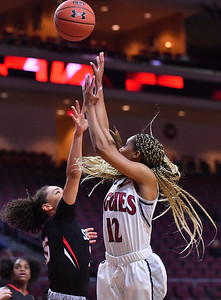 LAS VEGAS, NV - MARCH 09:  Zaire Williams #12 of the New Mexico State Aggies shoots against Kamira Sanders #15 of the Seattle Redhawks during a semifinal game of the Western Athletic Conference basketball tournament at the Orleans Arena in Las Vegas, Nevada. Seattle won 84-61.