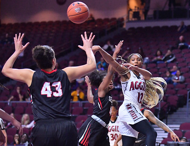LAS VEGAS, NV - MARCH 09:  Zaire Williams #12 of the New Mexico State Aggies passes against Joana Alves #43 of the Seattle Redhawks during a semifinal game of the Western Athletic Conference basketball tournament at the Orleans Arena in Las Vegas, Nevada. Seattle won 84-61.