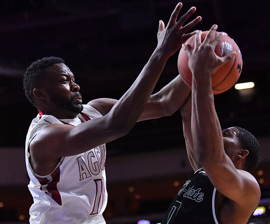 LAS VEGAS, NV - MARCH 08:  Johnathon Wilkins #11 of the New Mexico State Aggies battles Glen Burns #0 of the Chicago State Cougars for a rebound during a quarterfinal game of the Western Athletic Conference basketball tournament at the Orleans Arena in Las Vegas, Nevada. The Aggies won 97-70.