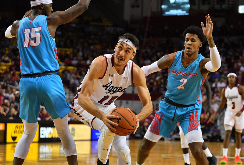 LAS CRUCES, NEW MEXICO - NOVEMBER 21, 2019:  Ivan Aurrecoechea #15 of the New Mexico State Aggies looks to shoot against Carlton Bragg Jr. #15 and Vance Jackson #2 of the New Mexico Lobos during their game at The Pan American Center on November 20, 2019 in Las Cruces, New Mexico. The Lobos defeated the Aggies 78-77.  (Photo by Sam Wasson/bleedCrimson.net)