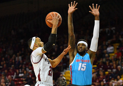 LAS CRUCES, NEW MEXICO - NOVEMBER 21, 2019:  Trevelin Queen #21 of the New Mexico State Aggies shoots against Carlton Bragg Jr. #15 of the New Mexico Lobos during their game at The Pan American Center on November 21, 2019 in Las Cruces, New Mexico. The Lobos defeated the Aggies 78-77.  (Photo by Sam Wasson/bleedCrimson.net)