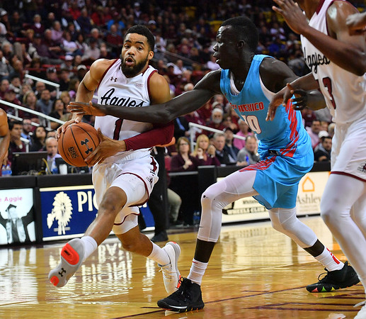 LAS CRUCES, NEW MEXICO - NOVEMBER 21, 2019:  Shunn Buchanan #1 of the New Mexico State Aggies drives against Makuach Maluach #10 of the New Mexico Lobos during their game at The Pan American Center on November 21, 2019 in Las Cruces, New Mexico. The Lobos defeated the Aggies 78-77.  (Photo by Sam Wasson/bleedCrimson.net)
