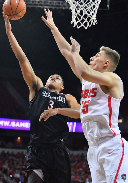 LAS VEGAS, NV - MARCH 10:  Trey Kell #3 of the San Diego State Aztecs shoots against Vladimir Pinchuk #15 of the New Mexico Lobos during the championship game of the Mountain West basketball tournament at the Thomas & Mack Center in Las Vegas, Nevada. San Diego State won 82-75.  (Photo by Sam Wasson)