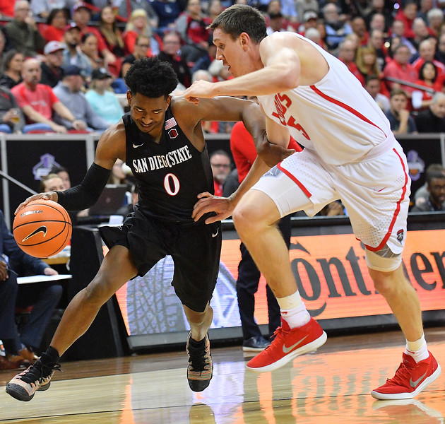 LAS VEGAS, NV - MARCH 10:  Devin Watson #0 of the San Diego State Aztecs drives against Joe Furstinger #5 of the New Mexico Lobos during the championship game of the Mountain West basketball tournament at the Thomas & Mack Center in Las Vegas, Nevada. San Diego State won 82-75.  (Photo by Sam Wasson)