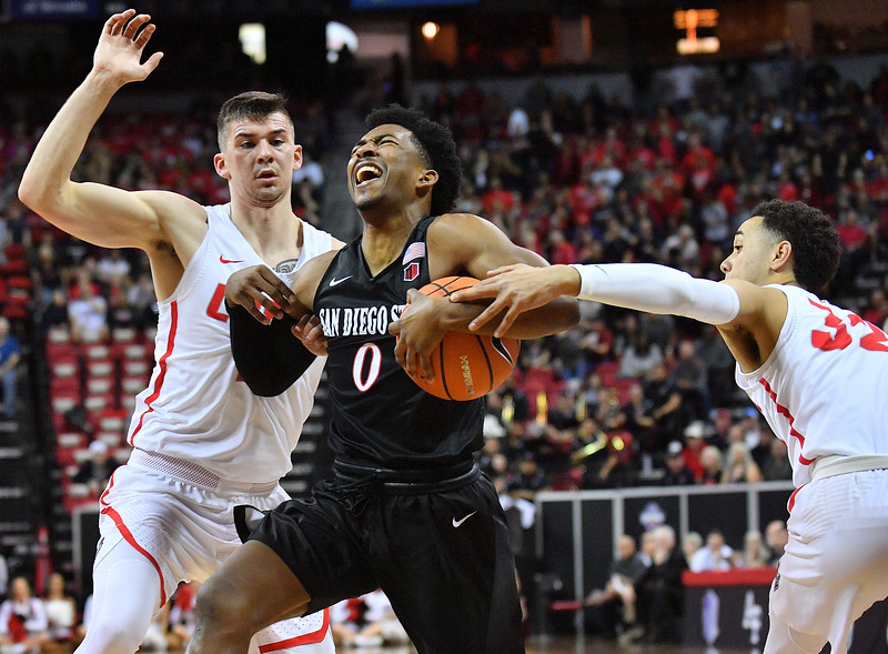 LAS VEGAS, NV - MARCH 10:  Devin Watson #0 of the San Diego State Aztecs is fouled by Anthony Mathis #32 of the New Mexico Lobos during the championship game of the Mountain West basketball tournament at the Thomas & Mack Center in Las Vegas, Nevada. San Diego State won 82-75.  (Photo by Sam Wasson)