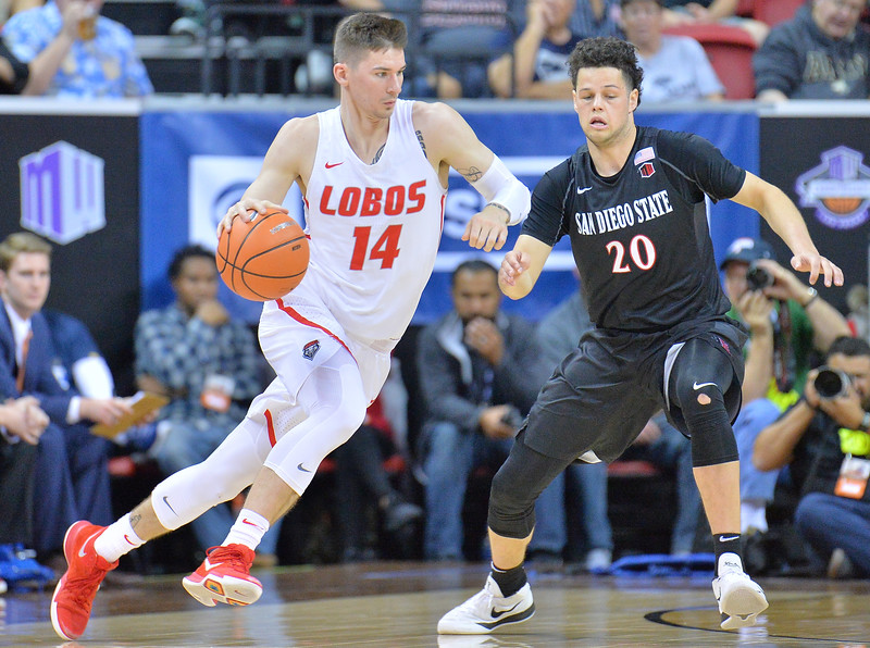 LAS VEGAS, NV - MARCH 10:  Dane Kuiper #14 of the New Mexico Lobos drives against Jordan Schakel #20 of the San Diego State Aztecs during the championship game of the Mountain West basketball tournament at the Thomas & Mack Center in Las Vegas, Nevada. San Diego State won 82-75.  (Photo by Sam Wasson)
