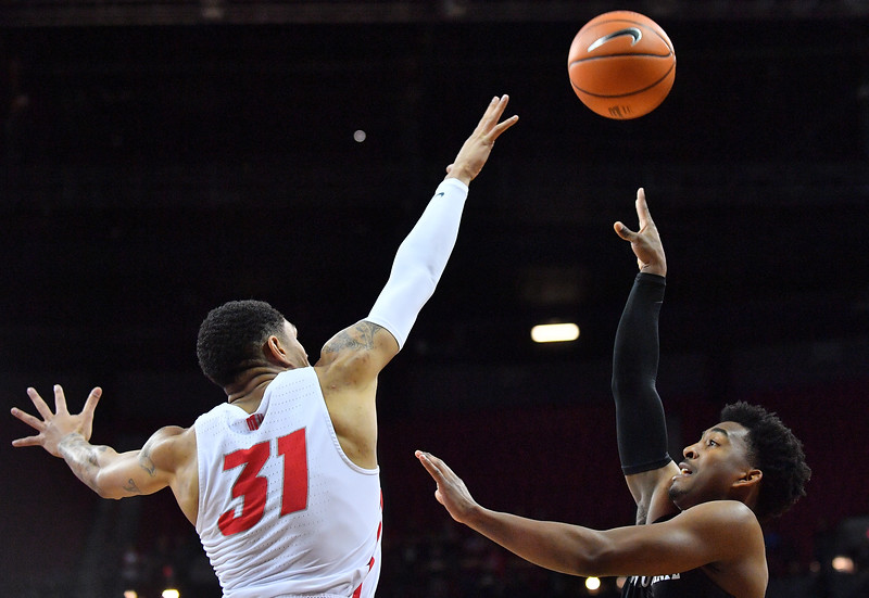 LAS VEGAS, NV - MARCH 10:  Devin Watson #0 of the San Diego State Aztecs shoots against Troy Simons #31 of the New Mexico Lobos during the championship game of the Mountain West basketball tournament at the Thomas & Mack Center in Las Vegas, Nevada. San Diego State won 82-75.  (Photo by Sam Wasson)