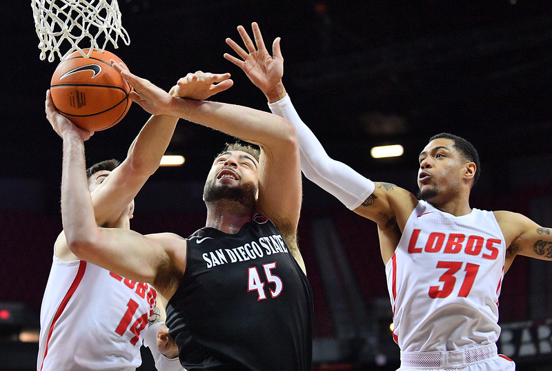 LAS VEGAS, NV - MARCH 10:  Dane Kuiper #14 of the New Mexico Lobos fouls Kameron Rooks #45 of the San Diego State Aztecs as Troy Simons #31 of the Lobos defends during the championship game of the Mountain West basketball tournament at the Thomas & Mack Center in Las Vegas, Nevada. San Diego State won 82-75.  (Photo by Sam Wasson)