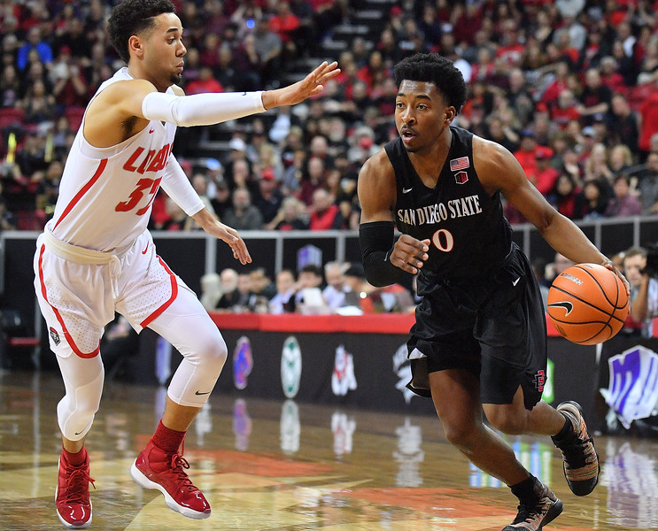 LAS VEGAS, NV - MARCH 10:  Devin Watson #0 of the San Diego State Aztecs drives against Anthony Mathis #32 of the New Mexico Lobos during the championship game of the Mountain West basketball tournament at the Thomas & Mack Center in Las Vegas, Nevada. San Diego State won 82-75.  (Photo by Sam Wasson)