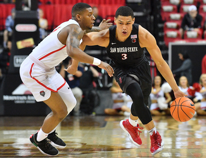LAS VEGAS, NV - MARCH 10:  Trey Kell #3 of the San Diego State Aztecs dribbles against Chris McNeal #1 of the New Mexico Lobos during the championship game of the Mountain West basketball tournament at the Thomas & Mack Center in Las Vegas, Nevada. San Diego State won 82-75.  (Photo by Sam Wasson)