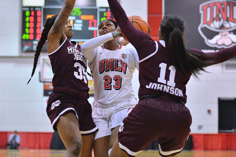 Dec 20, 2017; Las Vegas, NV, USA;  UNLV Rebels forward Jordyn Bell (23) drives in for a shot against Mississippi State Bulldogs guard Victoria Vivians (35) and Mississippi State Bulldogs guard Roshunda Johnson (11) during the Duel In The Desert at the Cox Pavilion in Las Vegas, Nevada.  Photo by Sam Wasson for UNLV Athletics