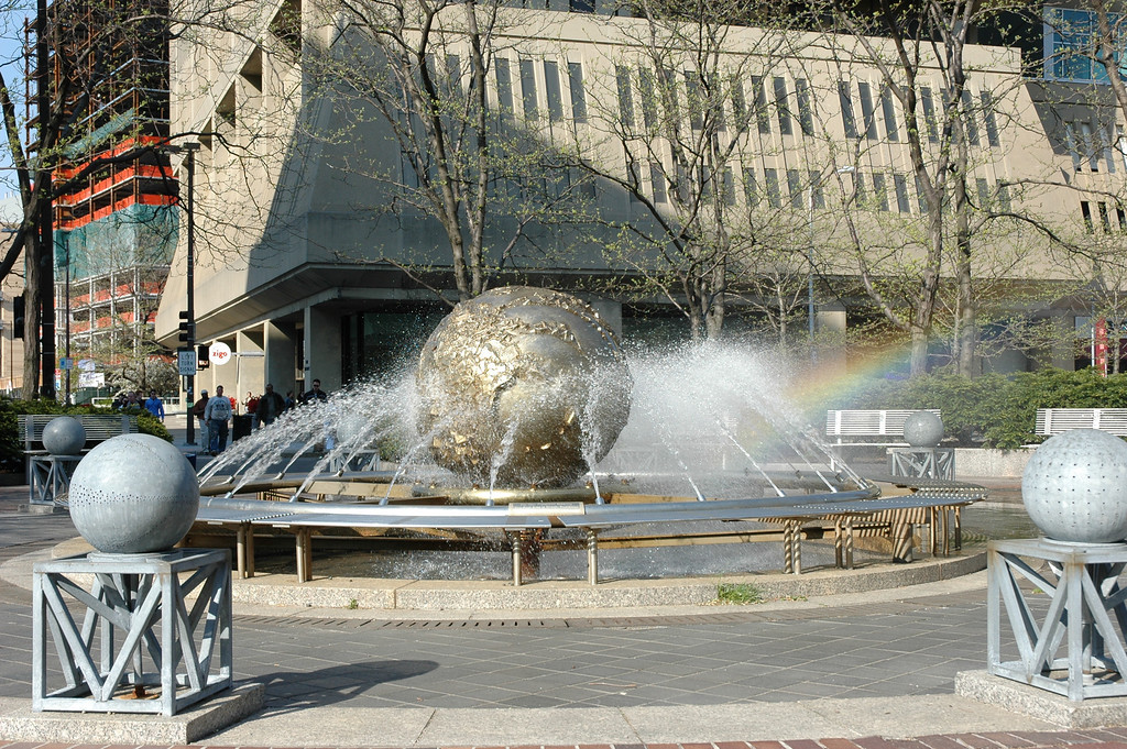 "The ""Steaming Globe"" in Kendall Square near my place of employment.  It was windy, so the periodic gusts caused rainbows to emanate from the streams of water."