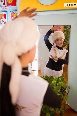 Kara Jorgo dancer in traditional costume posing in front of a mirror in Jyrgalan Kyrgyzstan