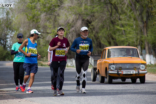 marathon runners with a car passing