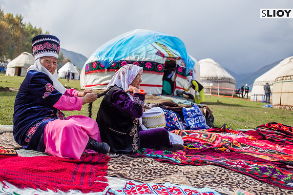 Two Kyrgyz ejes sit in front of a group of yurt tents on Jailoo Kyrchyn during the World Nomad Games 2016 in Kyrgyzstan.