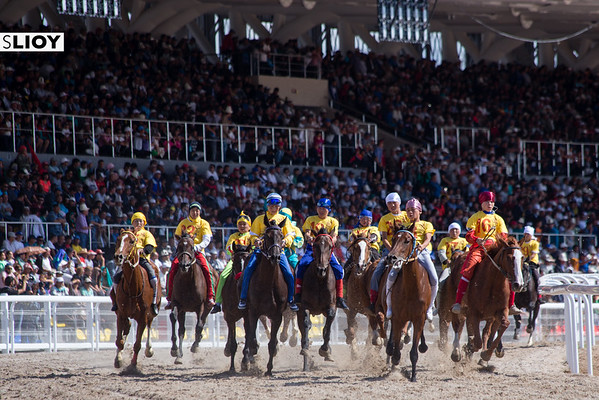 The crowded fields of At Chabysh racers turning a corner in front of the hippodrome stadium at the 2016 World Nomad Games in Kyrgyzstan.