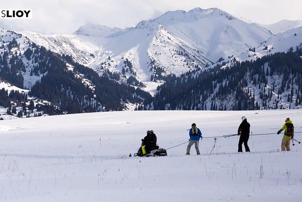 Free-Ride Skiiers Being Pulled By A Snowmobile In The Tian Shan Mountains Near Jyrgalan Village in the Issyk-Kol region of Kyrgyzstan.