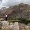 A hiker overlooking Snake Lake near Iskender Kul in Tajikistan's Fann Mountains.