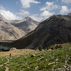 A solo hiker ascends from the Kulikalon Lakes towards the Chukurak Pass in the Fann Mountains of Tajikistan.