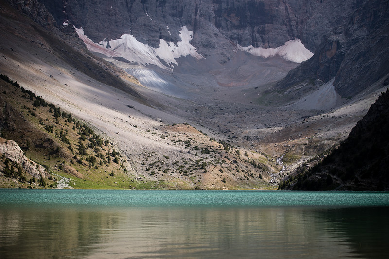 View of the largest Kulikalon Lake and backing rock wall in the Fann Mountains of Tajikistan.