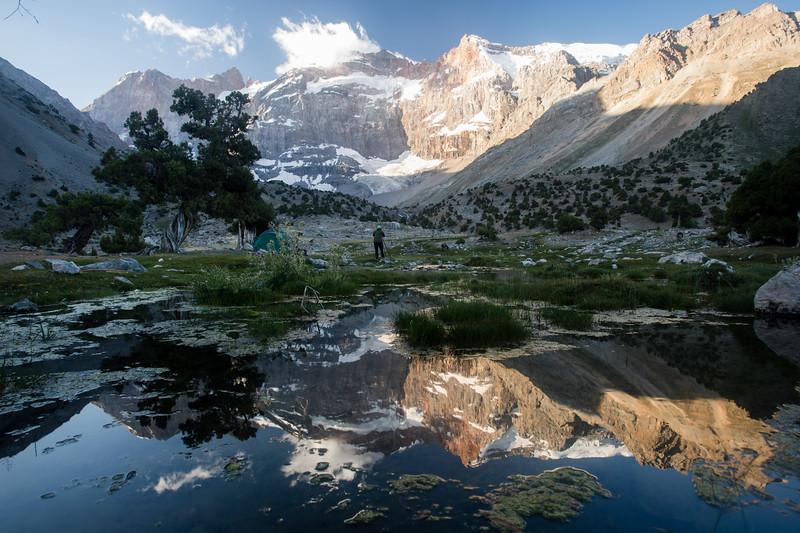 Sunlight illuminates the peaks of the Chimtarga Ridge at the southern edge of the Kulikalon Valley in Tajikistan's Fann Mountains.