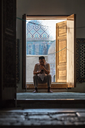 A pilgrim stops for a break in a doorframe at the Shah-i-Zinda Mausoleum complex in Samarkand, Uzbekistan.