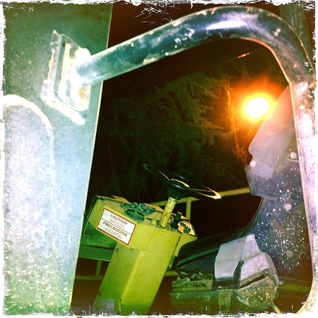 The cockpit of some street paving machinery lit by a street light.