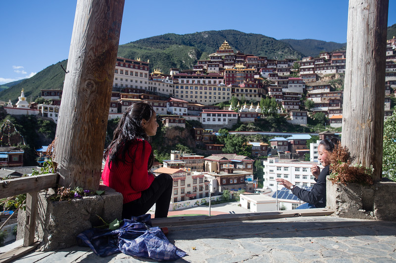 Two local girls sitting in a pagoda above the temples of Baiyu in Sichuan, China.