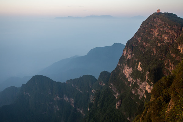 A lone hilltop temple on the peak of Emei Buddhist Holy Mountain as the sun rises over the plains of Sichuan, China.