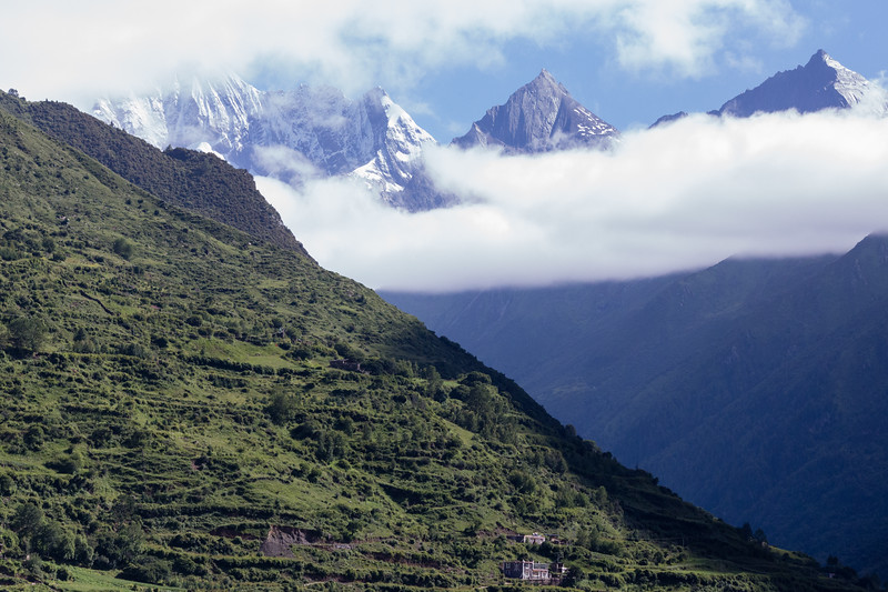 A small house beneath the looming peaks of Four Sisters Mountain in Sichuan, China.