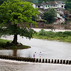 A young Chinese couple crossing the river in Liujiang old town in Sichuan, China.
