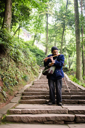 A man plays the flute on a stairway of Qingcheng holy Taoist mountain in Sichuan, China.
