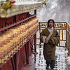 A pilgrim circumambulates the prayer wheels of a small chapel at Drigung Til Monastery in the U region of Tibet.