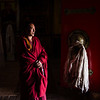 A monk stands just inside the door of a chapel at Pomda Monastery in the Chamdo Prefecture of Eastern Tibet.