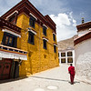 A young monk walks the alleys between monastery buildings at Sera Monastery on the outskirts of Lhasa, Tibet.