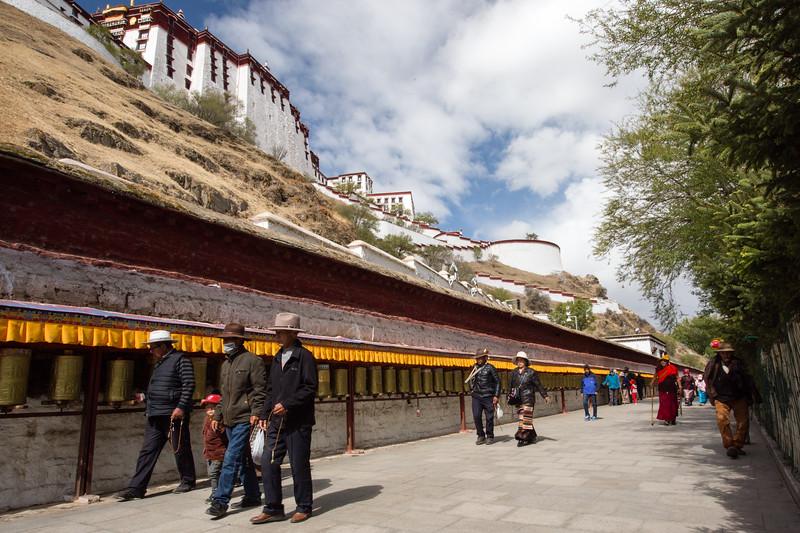 Pilgrims circumambulate the kora of the Potala Palace in Lhasa, Tibet.