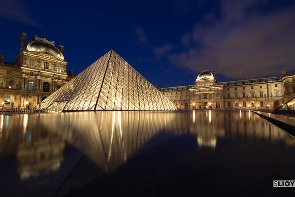 Louvre museum pyramid in paris at night.