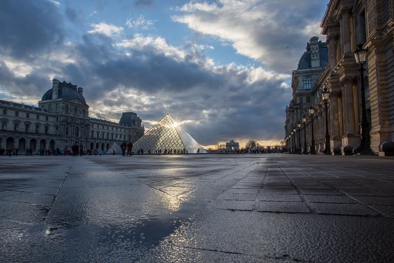 Louvre museum pyramid in paris at sunset.