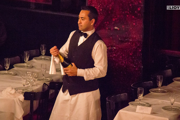 waiter opening champagne at paradis latin