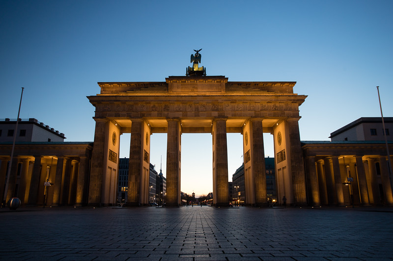 The Brandenburg Gate is lit as the sun rises over Berlin, Germany.