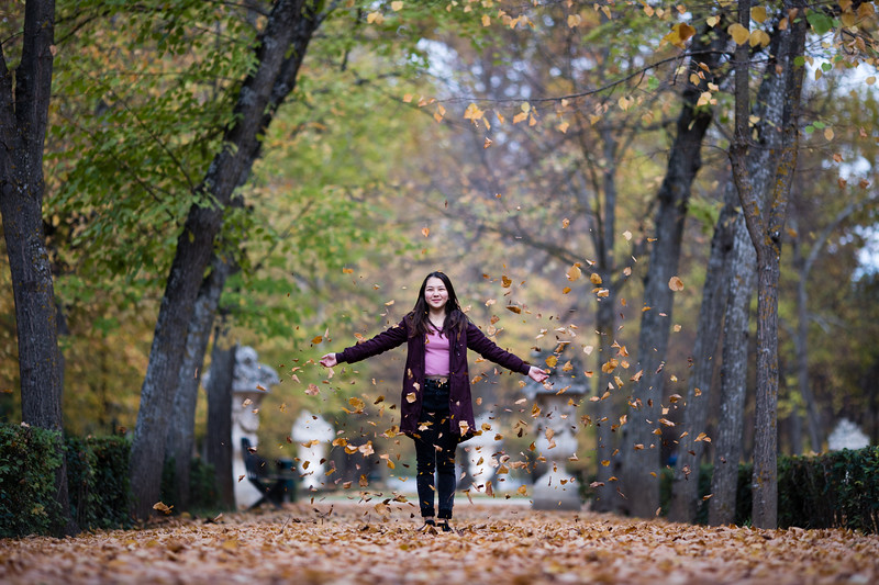 A young female tourist playing in the leaves of the Jardin del Principe  of Aranjuez during the fall in Spain.