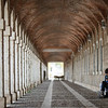 A local couple sits in arcades outside the Royal Palace of Aranjuez in Spain.