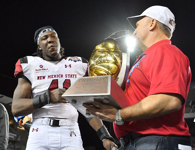 December 29, 2017; Tucson, AZ, USA;  New Mexico State Aggies linebacker Leon McQuaker (41) looks at the championship trophy after his team defeated the Utah State Aggies 26-20 in overtime at the NOVA Home Loans Arizona Bowl at Arizona Stadium in Tucson, Ariz.  Photo by Sam Wasson/bleedCrimson.net