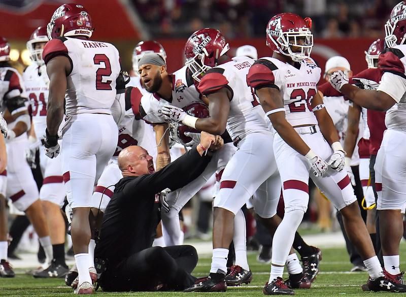 December 29, 2017; Tucson, AZ, USA;  New Mexico State Aggies linebackers/special teams coach Oliver Soukup celebrates with his team after a missed field goal by Utah State Aggies place kicker Dominik Eberle (62) during the NOVA Home Loans Arizona Bowl at Arizona Stadium in Tucson, Ariz.  Photo by Sam Wasson/bleedCrimson.net