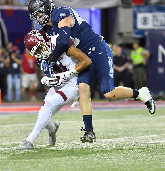 December 29, 2017; Tucson, AZ, USA;  New Mexico State Aggies wide receiver Anthony Muse (21) is tackles by Utah State Aggies linebacker Chase Christiansen (48) during the NOVA Home Loans Arizona Bowl at Arizona Stadium in Tucson, Ariz.  Photo by Sam Wasson/bleedCrimson.net