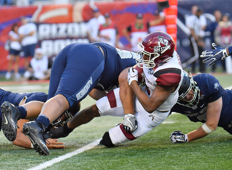 December 29, 2017; Tucson, AZ, USA;  New Mexico State Aggies running back Larry Rose III (3) is tackled by Utah State Aggies nose tackle Gasetoto Schuster (56) during the NOVA Home Loans Arizona Bowl at Arizona Stadium in Tucson, Ariz.  Photo by Sam Wasson/bleedCrimson.net