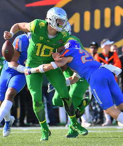 Dec 16, 2017; Las Vegas, NV, USA;  Oregon Ducks quarterback Justin Herbert (10) fumbles the ball as he's hit by Boise State Broncos safety Kekaula Kaniho (28) during their game at the 26th Las Vegas Bowl at Sam Boyd Stadium. Boise State won 38-28.  Photo Credit: Sam Wasson for the Portland Tribune