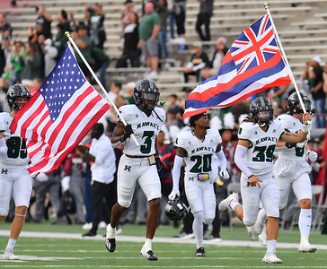 LAS CRUCES, NEW MEXICO - SEPTEMBER 25:  The Hawaii Rainbow Warriors run onto the field carrying Hawaiian and American flags before the start of their game against the New Mexico State Aggies at Aggie Memorial Stadium on September 25, 2021 in Las Cruces, New Mexico.  (Photo by Sam Wasson/bleedCrimson.net)